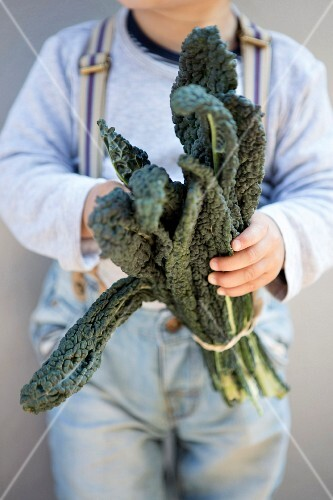 A man holding a bundle of kale