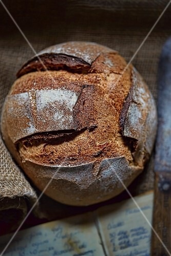 A rustic loaf of bread with an old cookbook and a knife