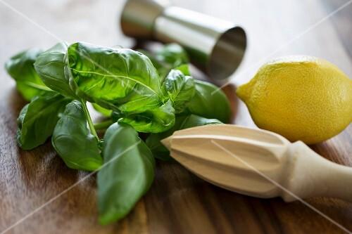 Ingredients for Gin Basil Smash: lemons, basil, a measuring cup and a wooden lemon juicer