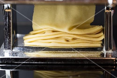 Fresh pasta dough being passed through a pasta machine