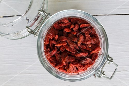Goji berries in a flip-top jar on a white wooden surface