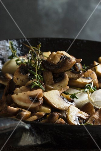 Fried mushrooms with thyme in a cast iron pan