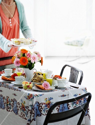 A table laid for breakfast with a bunch of colourful gerberas and a woman holding a plate of muffins