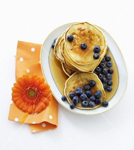 Mini pancakes with blueberries and maple syrup
