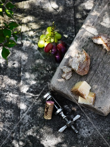 A rustic platter with cheese and pieces of bread on a stone surface