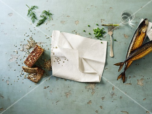 an arrangement of smoked mackerel, wholemeal bread and a white napkin