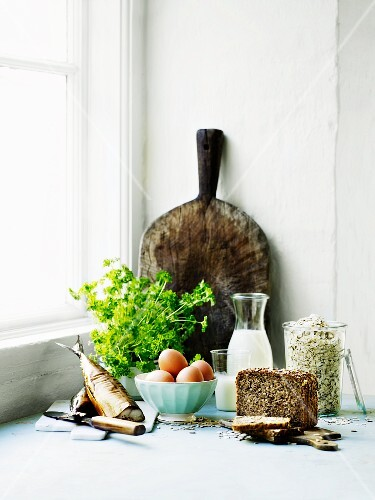 An arrangement of smoked fish, a bunch of parsley, bread and a rustic wooden chopping board