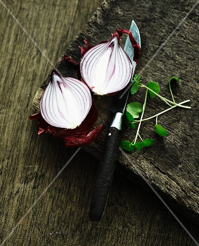 A halved red onion on a wooden chopping board