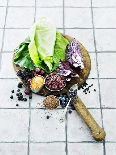 An arrangement of different types of cabbages, legumes and berries