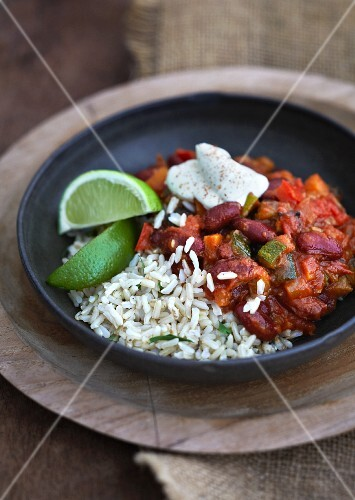 Mexican bean chili with rice, sour cream and lime