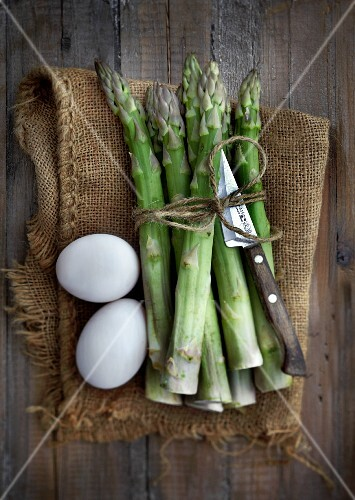 Green asparagus and eggs on a jute sack