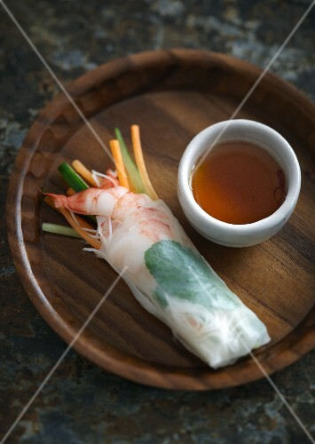 A spring roll with a prawn and vegetables filling served with soy sauce