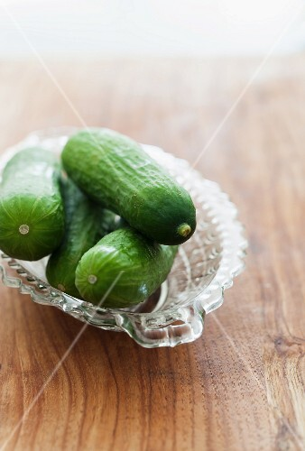Fresh mini cucumbers in a glass bowl