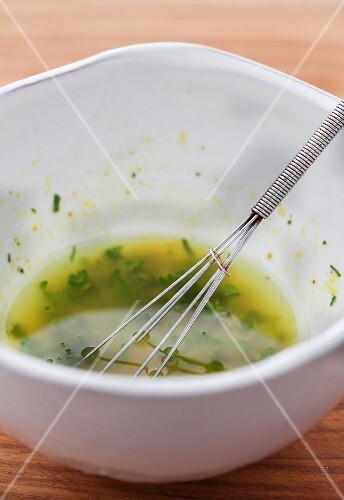 Dressing with fresh herbs and a whisk in a bowl