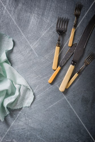 Vintage cutlery on a stainless steel surface
