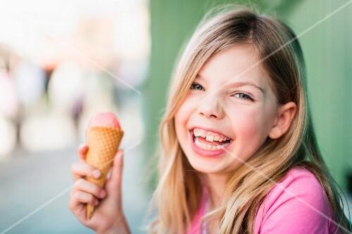 A little blonde girl eating an ice cream
