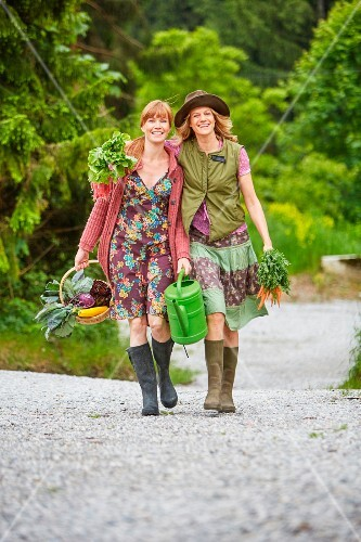 Two women carrying vegetables along a rural road
