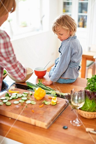 A mother and son preparing vegetables in a kitchen