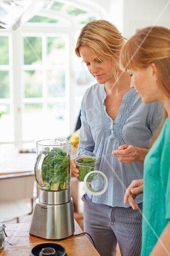Women preparing a green vegan smoothie in a kitchen