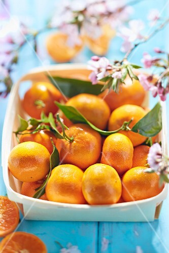 Mandarins with leaves in a wooden basket