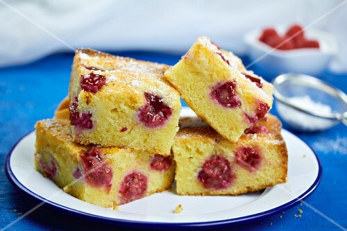 Slices on raspberry cake dusted with icing sugar