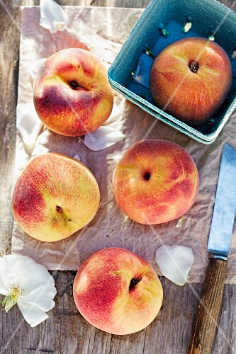 Peaches on a wooden table and in a cardboard dish