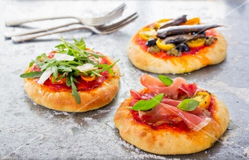 Three mini pizzas with different toppings