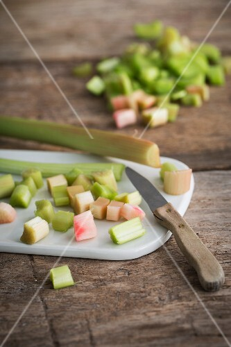 Peeled and chopped rhubarb on a ceramic board with a kitchen knife