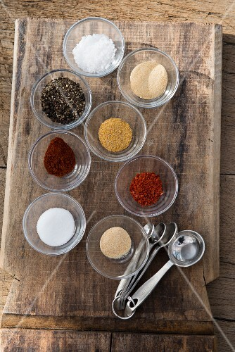 Bowls of various grill spices on a wooden board