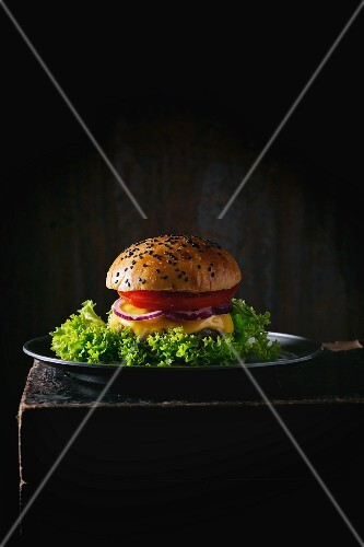 A homemade hamburger with black sesame seeds on a metal plate