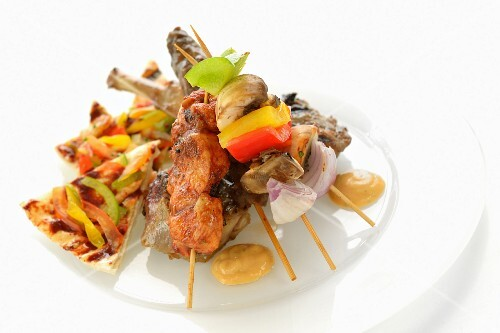 An Arabian grill platter with unleavened bread, grilled meat and grilled skewers