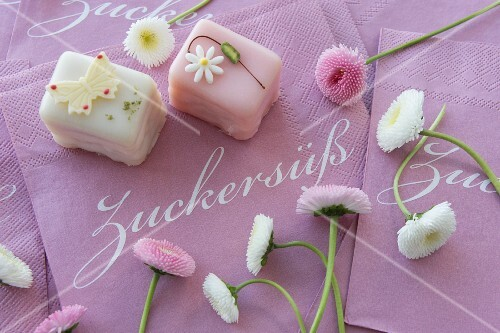 Petit fours with bellis on paper napkins