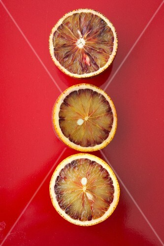 Three blood orange halves on a red surface