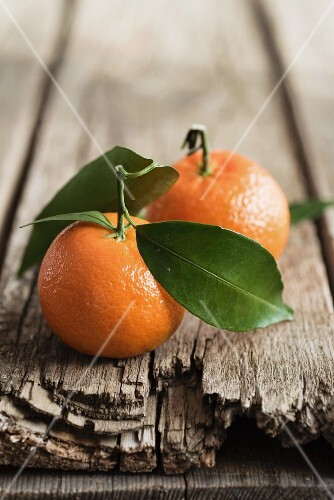 Two mandarins with leaves on a rustic wooden surface