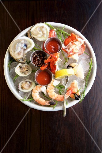 Oysters, prawns and crab with sauce and lemon on ice