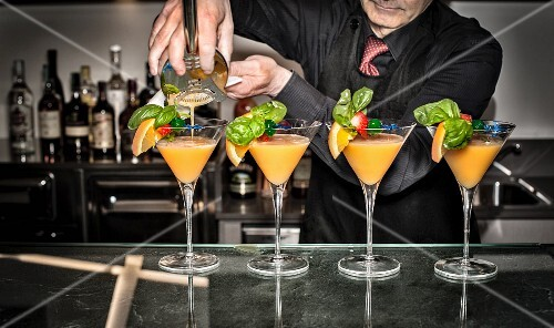 A barkeeper pouring cocktails from a shaker into glasses