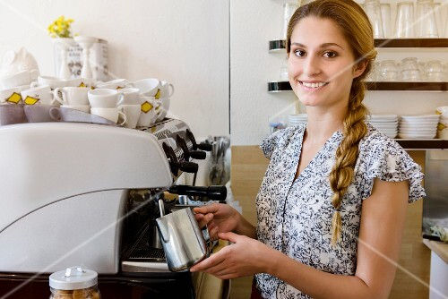 A young woman foaming milk at a coffee machine