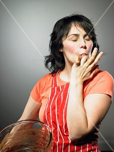 A woman licking out a bowl of chocolate with her fingers