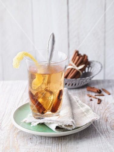 Mate tea punch with lemon zest and cinnamon sticks