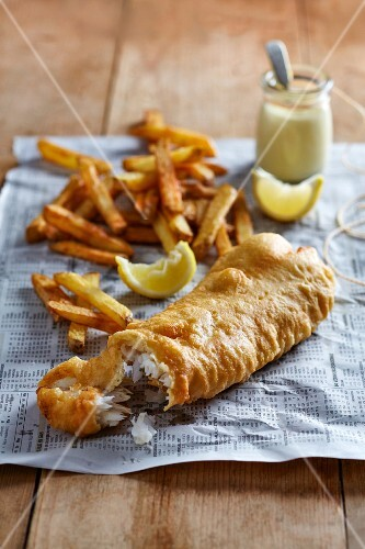 Fish and chips with lemon aioli on a piece of newspaper