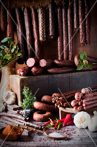 An arrangement of various game sausages, spices and herbs