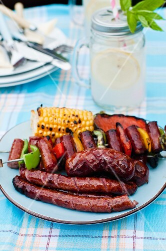 A barbecue platter with a grilled corn cob, a sausage skewer and sausages