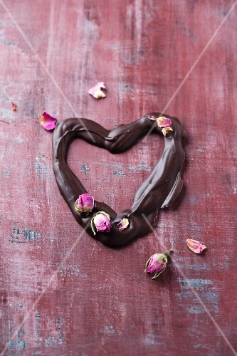 A chocolate heart with dried rose buds
