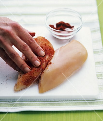 Chicken breast being rubbed with spices