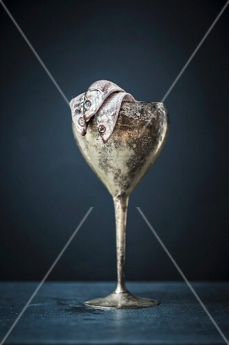 Anchovies in a metal goblet on a blue surface