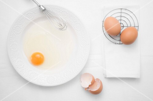 A broken egg on a plate with a whisk next whole eggs and egg shells