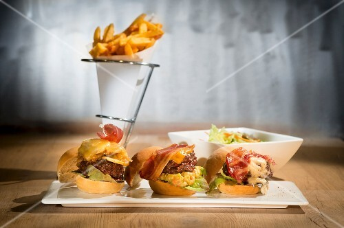 Three mini burgers on a serving platter with a cone of chips in the background