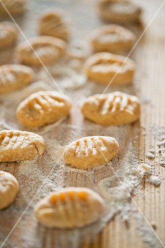Gnocchi with flour on a wooden board