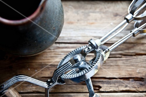 A vintage hand whisk next to a clay jug (detail)