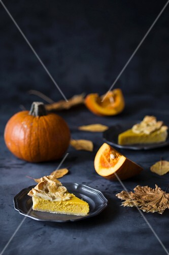 Slices of pumpkin pie decorated with pastry leaves on plates